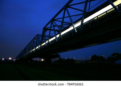 Light of a train on a railway bridge at night