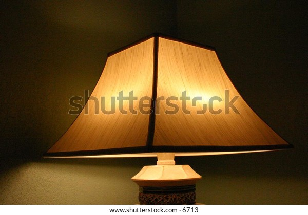 light under lampshade in dimly lit room
