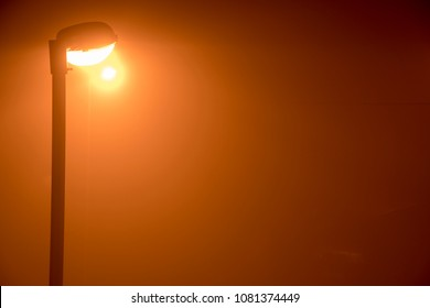 light view on the street with a yellow street light on the left side of the frame surrounded by the fog from the pollution of the air,  vertical composition