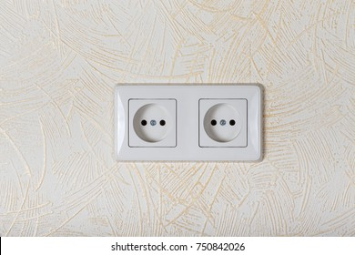 Light wallpaper on a wall with electrical outlet for background. Close Up detail.