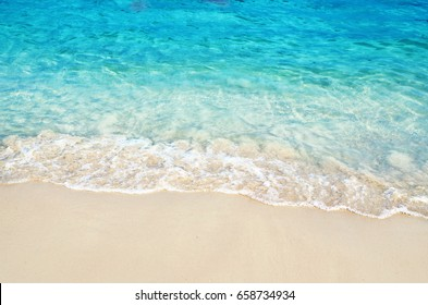 light wave at the sea and sandy beach in summer time