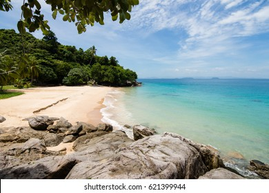 Light waves of idyllic turquoise sea meets small sheltered golden sand beach on a paradise island. Perhentian islands, Malaysia.