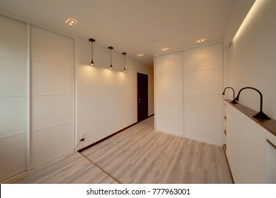 The light white bedroom with the white built-in sliding wardrobes and lamps