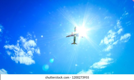 Light white clouds in the blue of the sky cuts through the elegant silhouette of the aircraft, illuminated by the sun.