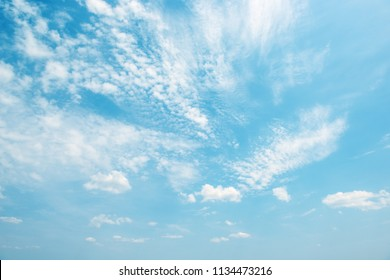 Light white clouds in bright blue sky. Copy space for text