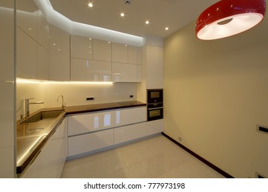 Light white kitchen with a white floor and a black working surface