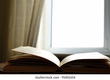 Light window, curtain and the opened book on a table