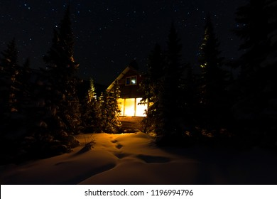 Light from the window of a forest hut under the night sky of the milky way in the winter forest