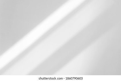 The light from the window shines on the wall, the shadow lines from the curtain, blurry shadows and silates on the wall.