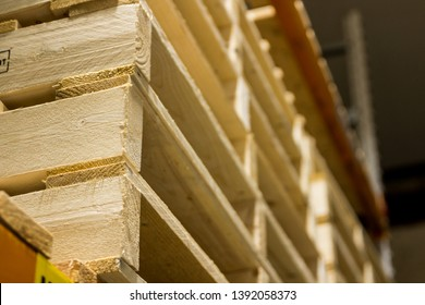 Light wood cargo pallets stacked high in a dirty factory neatly and cleanly on red industrial shelfs. Well built commercial freight pallets used internationally in shipping and commerce.