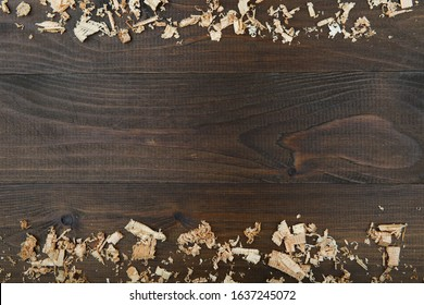 light wood shavings on dark wooden background flat lay with copy space