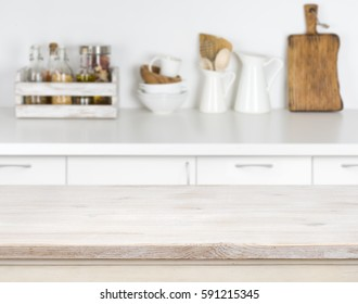 Light wood table with bokeh image of kitchen counter interior.