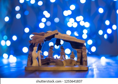 Light wooden christmas crib on bokeh background