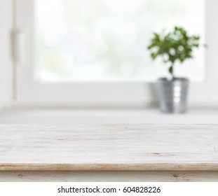 Light wooden texture table on defocuced summer window background.