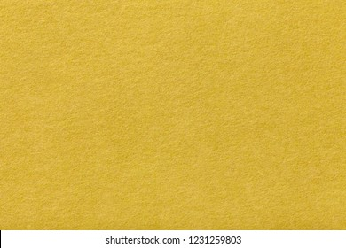 Light yellow matte background of suede fabric, closeup.