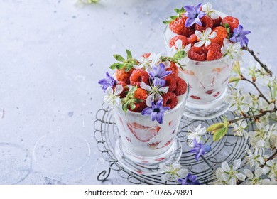 light yogurt without sugar with fresh berries on a light background with cherry blossoms. Diet food in glasses
