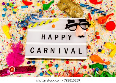 Lightbox with letters - HAPPY CARNIVAL - on colorful festive party decoration with steamers, confetti and balloons.