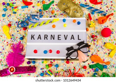 Lightbox with letters - KARNEVAL means HAPPY CARNEVAL - on colorful festive party decoration with steamers, confetti and ballons.