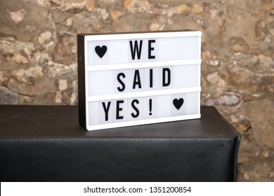 Lightbox /lightboard with text: We said yes! on black underground and stone wall in background.