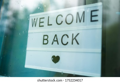 Lightbox with a sign WELCOME BACK behind a glass door of the cafe during the rain. We're open again after quarantine, photo of small business owner. Please wear a face mask and keep your distance to