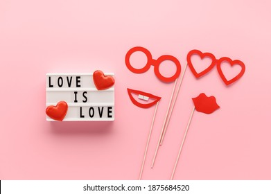 Lightbox with slogan LOVE HAS NO GENDER, red paper props glasses and lips on pastel pink background. Concept Homosexuality, lesbian love. Top view, creative flat lay. Holiday Greeting card
