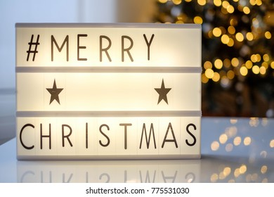 lightbox with text merry christmas and led lights blurred bokeh background, christmas decoration