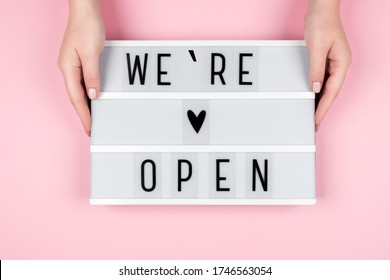 Lightbox with the text WE OPENED on a pink background in the hands of women. The owner of the hotel, beauty salon, restaurant informs customers about the opening - Shutterstock ID 1746563054