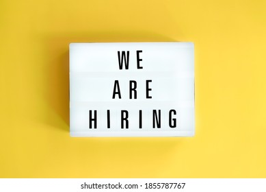 Lightbox with a words text We Are Hiring board on yellow background.  Surviving economical and financial crisis. Job seeking, recruiting and business concept.