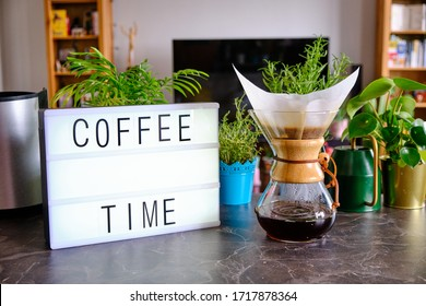 """Lightbox written """"Coffee Time"""". Home environment in the background. Concept for special brew coffee and making coffee at home."""