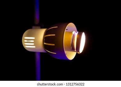 Lightbulb, bright yellow light. Isolated, black background.