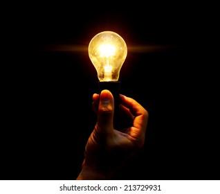 lightbulb held in hand on black background