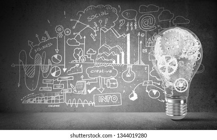Lightbulb with multiple gears inside placed against sketched business-analytical information on grey wall. 3D rendering.