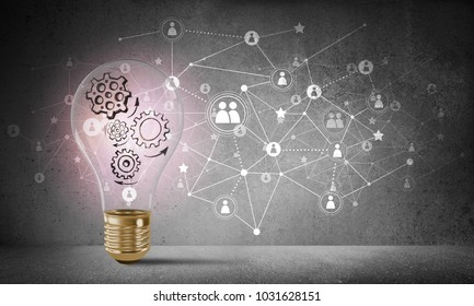 Lightbulb with multiple sketched gears inside placed against social network system drawn on grey wall. 3D rendering.