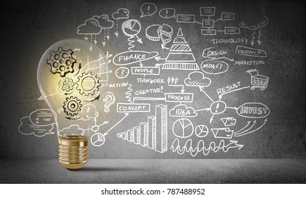 Lightbulb with multiple sketched gears inside placed against business-plan information drawn on grey wall. 3D rendering.