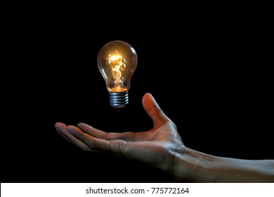 lightbulb on hand black background,abstract enegy magic concept