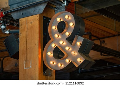 Lighted ampersand sign hanging from ceiling