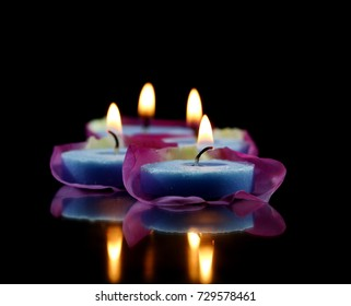 Lighted blue candles on Rose petals and black pebbles