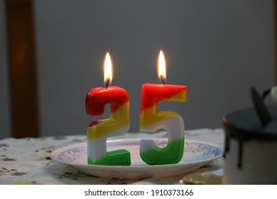 lighted or burning Candles with figures of two (2) and Five (5) together representing 25 years of age, or togetherness, or success, or foundation, silver jubilee celebrations