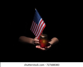 Lighted candle and female hands with USA flag.
