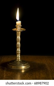 A lighted candle on a bronze candelabra
