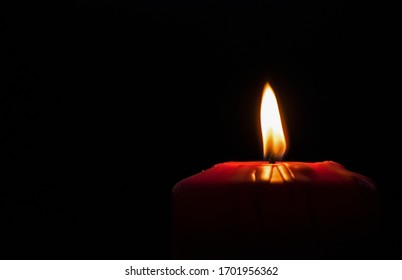 A lighted candle in someone's memory. Beautiful red holiday candle, on a black background. Christmas, Easter. Copy space.