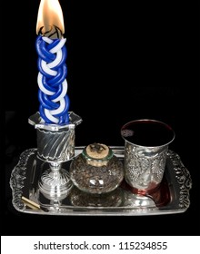 Lighted candle, spices, and kiddush cup with wine on a shiny silver tray. The havdala candle is lit after the conclusion of the jewish sabbath; wine is served and a sweet spice is smelled.