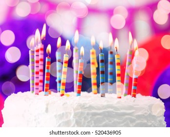 Lighted candles on birthday cake, closeup
