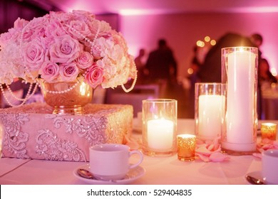 Lighted candles stand on the festive served dinner table