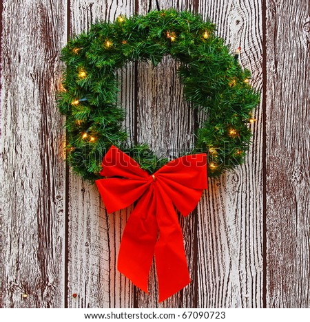 a lighted christmas wreath with a big red bow hanging outside with room for your text
