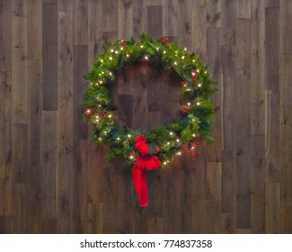 Lighted Christmas wreath isolated on a wood background with red ribbon