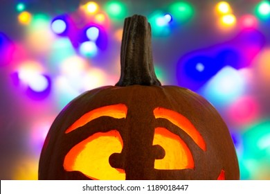 Lighted pumpkin face in front of a colorful background