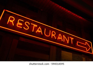 Lighted restaurant sign with arrow made of red fluorescent light in the wall with dark background
