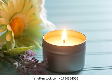 Lighted and Scented votive Candle in a tin holder with flowers on the side, all on teal boards table background with back window light area as copy space.  Horizontal photo with a front view