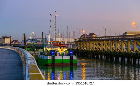 lighted ship in the harbor of Blankenberge at sunset, Belgian architecture of a popular town in Belgium